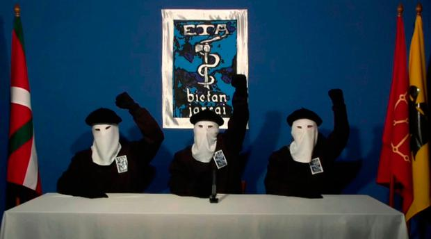 Masked ETA members raise their fists in unison following a news conference in 2011. The group yesterday announced that it had 'dissolved all its structures.' Photo: Gara via AP, File