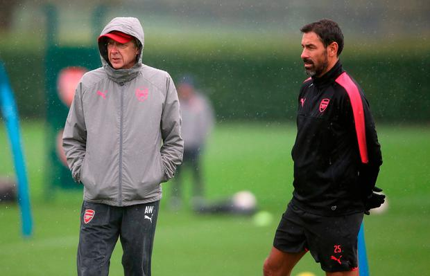 Arsene Wenger and Robert Pires look on as Arsenal's players go through their paces during training yesterday. Photo: John Walton/PA Wire