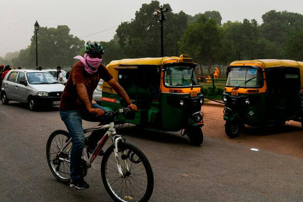 This photo taken on May 2, 2018 shows an Indian man covering as he cycles during a dust storm in New Delhi. Dust storms that tore across northern India killed at least 77 people and left 143 injured as trees and walls were brought down by powerful winds, officials said May 3. / AFP PHOTO / CHANDAN KHANNACHANDAN KHANNA/AFP/Getty Images