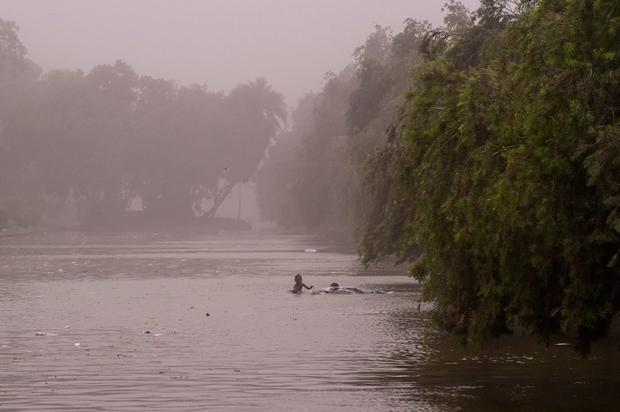 TOPSHOT - Indian children swim in a pond during a dust storm in New Delhi on May 2, 2018. Dust storms tore across northern India killing at least 77 people and injuring 143 as trees and walls were flattened by powerful winds, officials said May 3. / AFP PHOTO / CHANDAN KHANNACHANDAN KHANNA/AFP/Getty Images