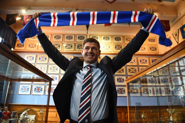 Former England and Liverpool captain Steven Gerrard smiles as he holds up a Rangers scarf in the trophy room as he is unveiled as Rangers' new manager (Photo by ANDY BUCHANAN / AFP)