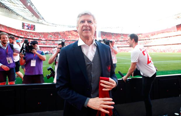 Arsenal manager Arsene Wenger takes his tie off to hand to a young fan