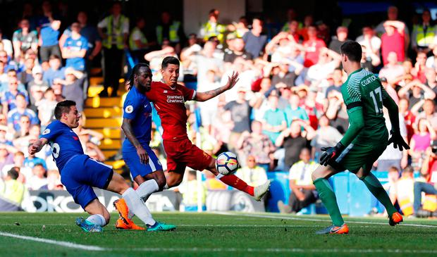 Chelsea's Cesar Azpilicueta diverts the ball back to Thibaut Courtois as Liverpool's Roberto Firmino and Chelsea's Victor Moses look on. Photo: Reuters
