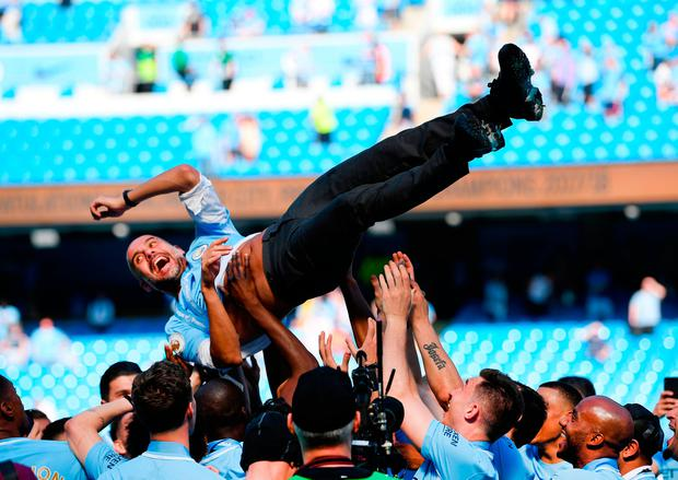 Pep Guardiola is lifted into the air during Manchester City's celebrations after their final home league game of the season. Photo by Shaun Botterill/Getty Images
