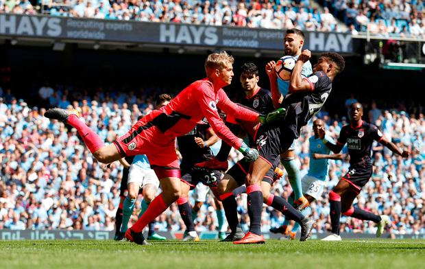 Huddersfield Town's Jonas Lossl in action with Steve Mounie and Manchester City's Nicolas Otamendi. Photo: Reuters