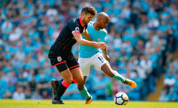 Manchester City's Fabian Delph (right) and Huddersfield Town's Tommy Smith battle for the ball. Photo credit: Martin Rickett/PA Wire