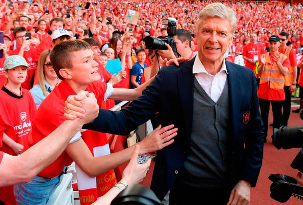 Arsene Wenger shakes hands with an Arsenal fan during his farewell at the Emirates Stadium. Photo by Mike Hewitt/Getty Images