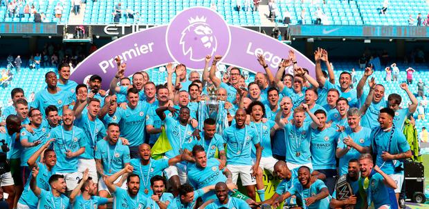 JOB DONE: Manchester City manager Pep Guardiola celebrates with players and staff during City's Premier League title coronation at the Etihad Stadium yesterday. Photo: PA