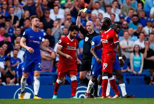 Liverpool's Mohamed Salah is shown a yellow card by referee Anthony Taylor for simulation