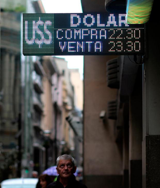 A man looks at an electronic board showing currency exchange rates in Buenos Aires' financial district, Argentina. Photo: Reuters