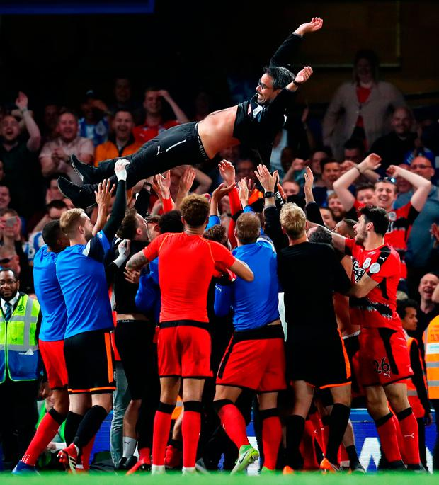 Huddersfield players throw their manager David Wagner into the air after they secured their Premier League status with a point against Chelsea. Photo: Getty