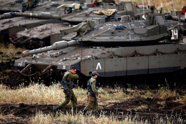 Israeli soldiers walk next to tanks near the Israeli side of the border with Syria in the Israeli-occupied Golan Heights. Photo: Reuters