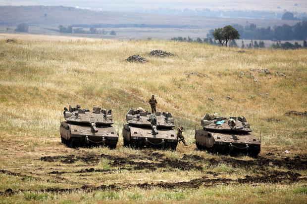 An Israeli soldier stands on a tank as another jumps off it near the Israeli side of the border with Syria in the Israeli-occupied Golan Heights, Israel May 9, 2018. REUTERS/Amir Cohen