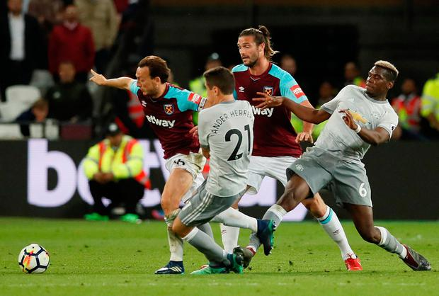 West Ham United's Mark Noble is challenged by Manchester United's Paul Pogba. Photo: Reuters