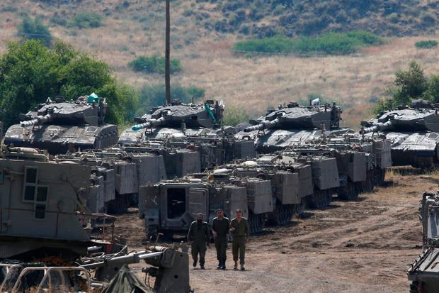 Israeli soldiers stroll among a build-up of tanks and armoured vehicles patrolling the Golan Heights. Photo: Reuters