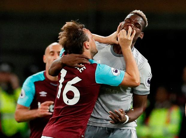 West Ham United's Mark Noble clashes with Manchester United's Paul Pogba