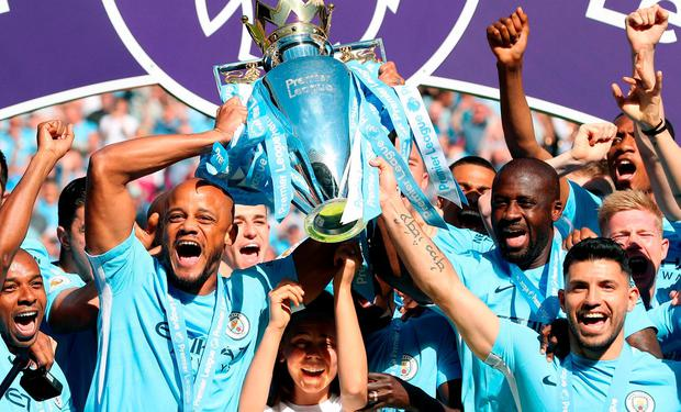 Manchester City's Vincent Kompany (left), Yaya Toure (second right) and Sergio Aguero lift the Premier League trophy after the Premier League match at the Etihad Stadium