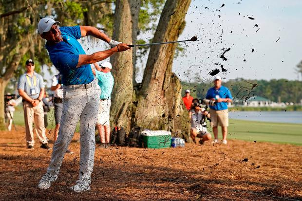 Rory McIlroy plays from the pine straw on the 18th hole