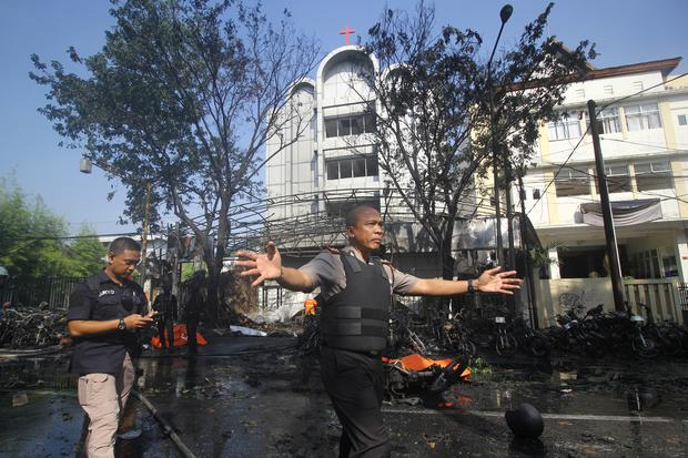 Police stand guard near the site of a blast at the Pentecost Church Central  Surabaya (
