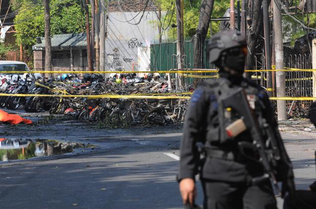 A police officer stands guard near the site where an explosion went off outside a church in Surabaya, East Java, Indonesia, Sunday, May 13, 2018. Multiple attacks including one by a suicide bomber disguised as a churchgoer targeted churches in Indonesia's second largest city of Surabaya early Sunday, killing a number of people and wounding dozens, police said. (AP Photo/Trisnadi)