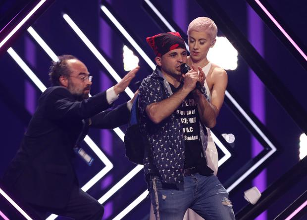 A man takes the microphone of SuRie from Great Britain, right, as a security staff approaches in Lisbon, Portugal, Saturday, May 12, 2018 during the Eurovision Song Contest grand final. (AP Photo/Armando Franca)
