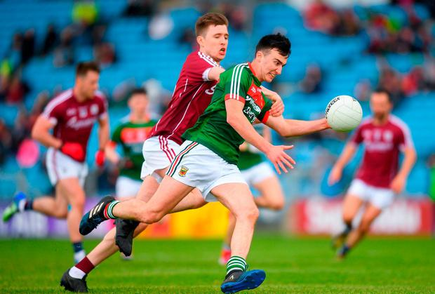 Mayo's Brendan Carr is put under pressure by Conor Brady of Galway. Photo: Eóin Noonan/Sportsfile