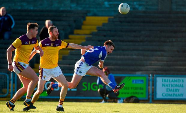 Ross Munnelly of Laois scores a point past Wexford defenders Alan Nolan and Naomhan Rossiter. Photo: Matt Browne/Sportsfile