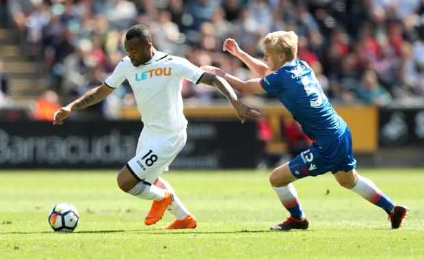 Swansea's Jordan Ayew keeps possession ahead of Stoke's Lasse Sorensen. Photo: Reuters