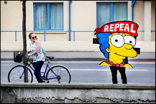 A cyclist passes a 'Repeal' supporter at Portobello in Dublin. Photo: Steve Humphreys