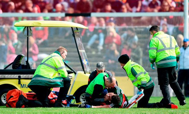 Medics attend to Tom Parsons after the Mayo man suffered a serious knee injury. Photo: David Fitzgerald/Sportsfile