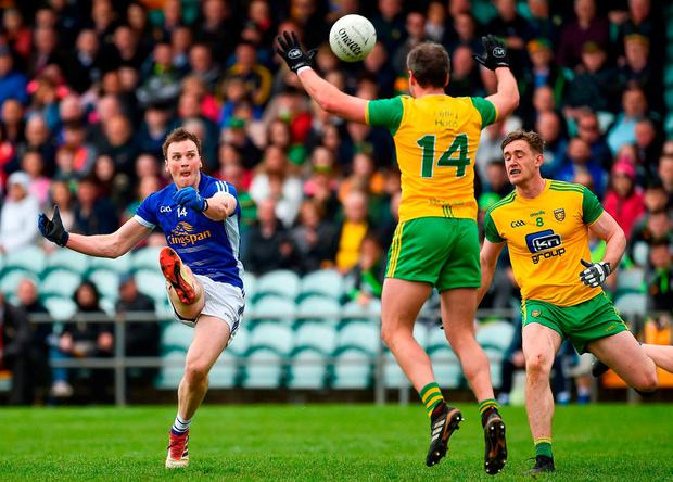 Gearoid McKiernan scores a point for Cavan despite the efforts of Michael Murphy. Photo: Oliver McVeigh/Sportsfile
