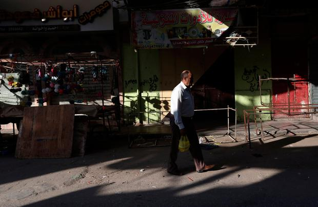 A Palestinian man walks past a closed shop during a general strike against the U.S. embassy move to Jerusalem and ahead of the 70th anniversary of Nakba, in Khan Younis in the southern Gaza Strip May 14, 2018. REUTERS/Ibraheem Abu Mustafa