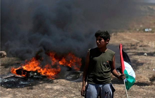 A boy holds a Palestinian flag in front of burning tires during a protest at the Gaza Strip's border with Israel, Monday, May 14, 2018. Israeli fire has killed dozens of Palestinians during mass protests along the Gaza border, marking the deadliest day of violence since a devastating 2014 cross-border war and casting a pall over Israel's festive inauguration of the new U.S. Embassy in contested Jerusalem. (AP Photo/Khalil Hamra)