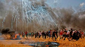Palestinians run from tear gas during clashes with Israeli security forces near the border between Israel and the Gaza Strip. Photo: AFP/Getty Images