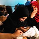The mother    of Leila Anwar al-Ghandour looks at her daughter as she is prepared for burial in Gaza City. Photo: Getty Images