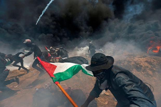 Palestinian demonstrators run for cover from Israeli fire and tear gas during a protest against the US embassy move. Photo: Reuters