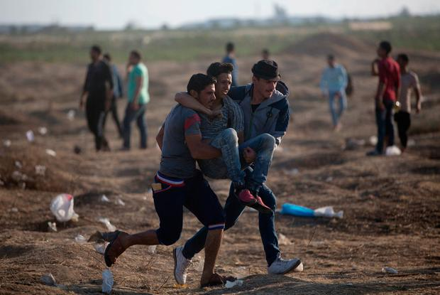 Palestinian protesters carry a wounded man shot by Israeli troops during a protest at the Gaza Strip's border with Israel, Tuesday, May 15, 2018. (AP Photo/Khalil Hamra)