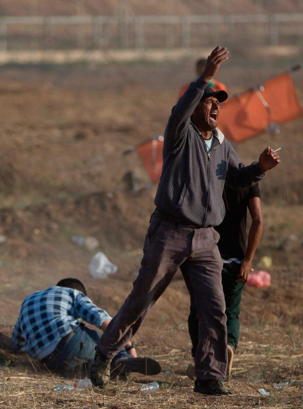 A Palestinian protester asks for help while standing next to a wounded man was shot by Israeli troops during a protest at the Gaza Strip's border with Israel, Tuesday, May 15, 2018. (AP Photo/Khalil Hamra)