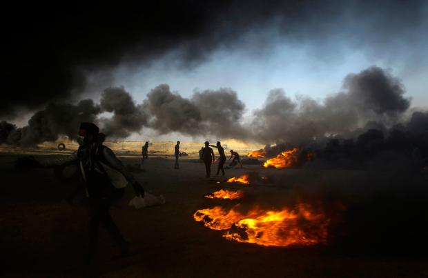 Palestinian protesters burn tires during a protest at the Gaza Strip's border with Israel, east of Khan Younis, Tuesday, May 15, 2018.. (AP Photo/Adel Hana)