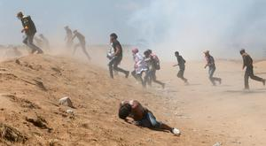 A Palestinian demonstrator reacts as others run from tear gas fired by Israeli forces during a protest marking the 70th anniversary of Nakba, at the Israel-Gaza border in the southern Gaza Strip May 15, 2018. REUTERS/Ibraheem Abu Mustafa