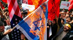 Demonstrators burn Israeli and US flags over the deaths of nearly 60 Palestinians on the Gaza border, during a protest inside the former US embassy in Tehran, Iran. Photo: AP