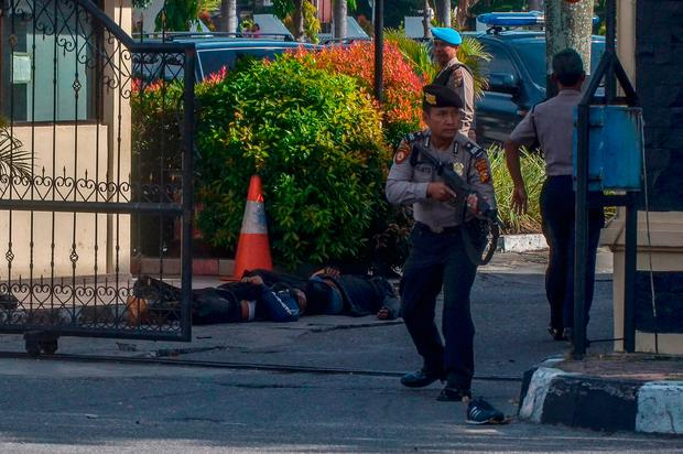 Two attackers lie dead as Indonesian policemen secure the site outside the police headquarters in Pekanbaru. Photo: Getty Images