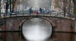 Cyclists ride on a bridge in central Amsterdam. Photo: Reuters/Yves Herman