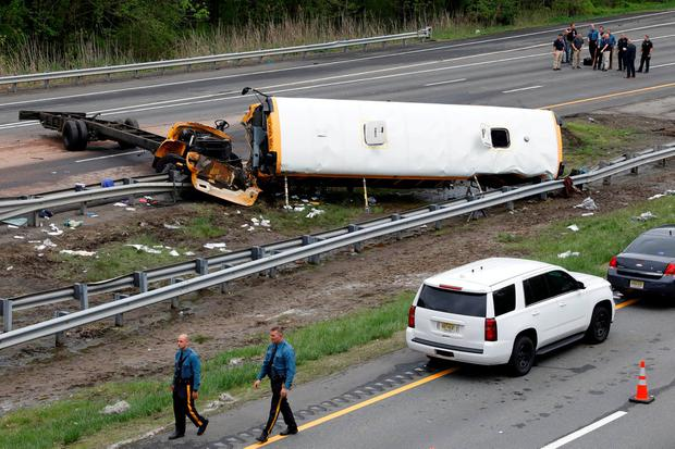 Police stand near the wreckage of a school bus on Interstate 80 following an accident with a dump truck in Mount Olive Township New Jersey U.S