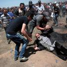 An elderly Palestinian man falls to the ground after being shot by Israeli troops during a protest at the Gaza Strip's border with Israel on Monday. Photo: Adel Hana/AP