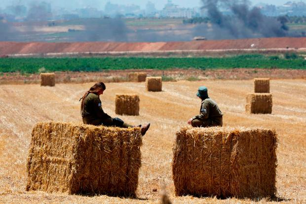 Israeli soldiers rest on bales of hay in a field overlooking the Gaza Strip as they man the border. Photo: Reuters