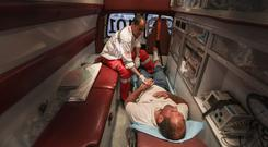 Medic Hussain Al-Smairy checks on a man inside an ambulance. There were 56 injuries reported among Gaza protesters Friday, mostly from tear gas, in contrast to thousands Monday. Photo by Wissam Nassar for The Washington Post