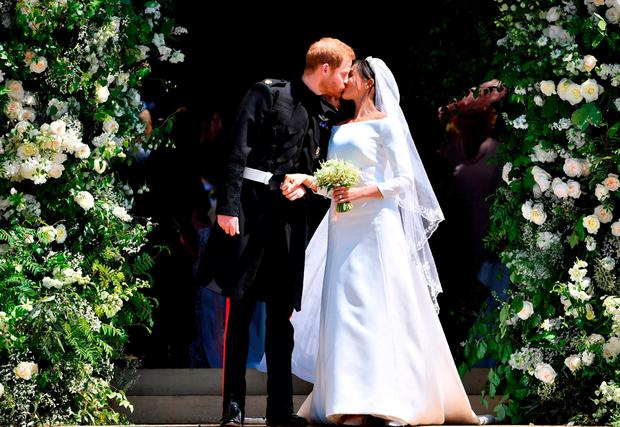 Prince Harry, Duke of Sussex kisses his wife Meghan, Duchess of Sussex, as they leave from the West Door of St George's Chapel, Windsor Castle. Photo: Ben Stansall, WPA Pool/Getty Images