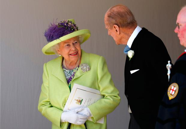 Queen Elizabeth talks with the Duke of Edinburgh after the wedding ceremony of her grandson Harry and Meghan. Photo: PA