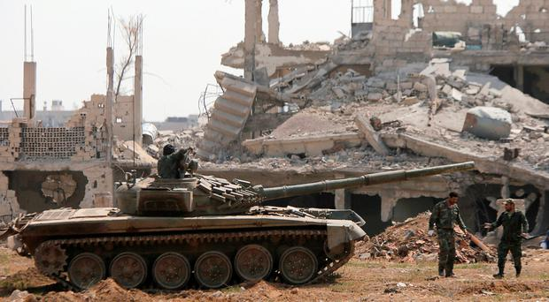 Isil evacuates enclave as Assad moves to reclaim Syrian capital
